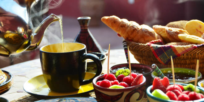 Setting of a traditional Moroccan breakfast with hot mint tea, fruits and baked goods.