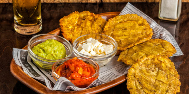 Some Costa Rican snacks (tostones or fried green plantain slices) served with guacamole and other sauces.