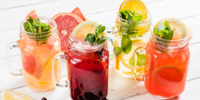 Four rustic glasses with colorful international summer drinks.