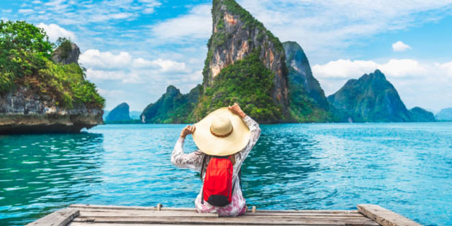 Traveler woman relaxing on wooden pier in a beautiful bay in Thailand while following her Southeast Asia travel guide.