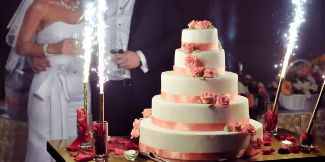 How to decorate a cake. Elegant white wedding cake with pink roses during wedding reception.