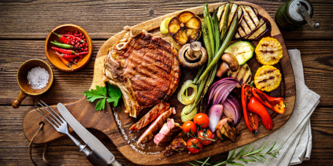 Grilled beef steak with grilled vegetables on serving board block after being prepared on cooking grills.